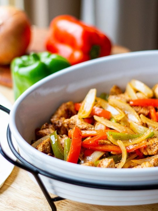 Baked Chicken Fajita mix in white casserole dish on butcherblock countertop with bell peppers and onions in background.