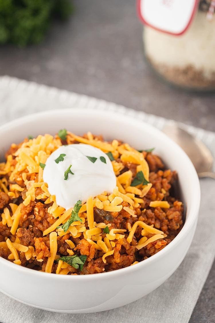 Shot of Beef Taco Rice Meal in a Jar made into a meal, in a white bowl, topped with shredded cheese and sour cream, garnished with fresh parsley.
