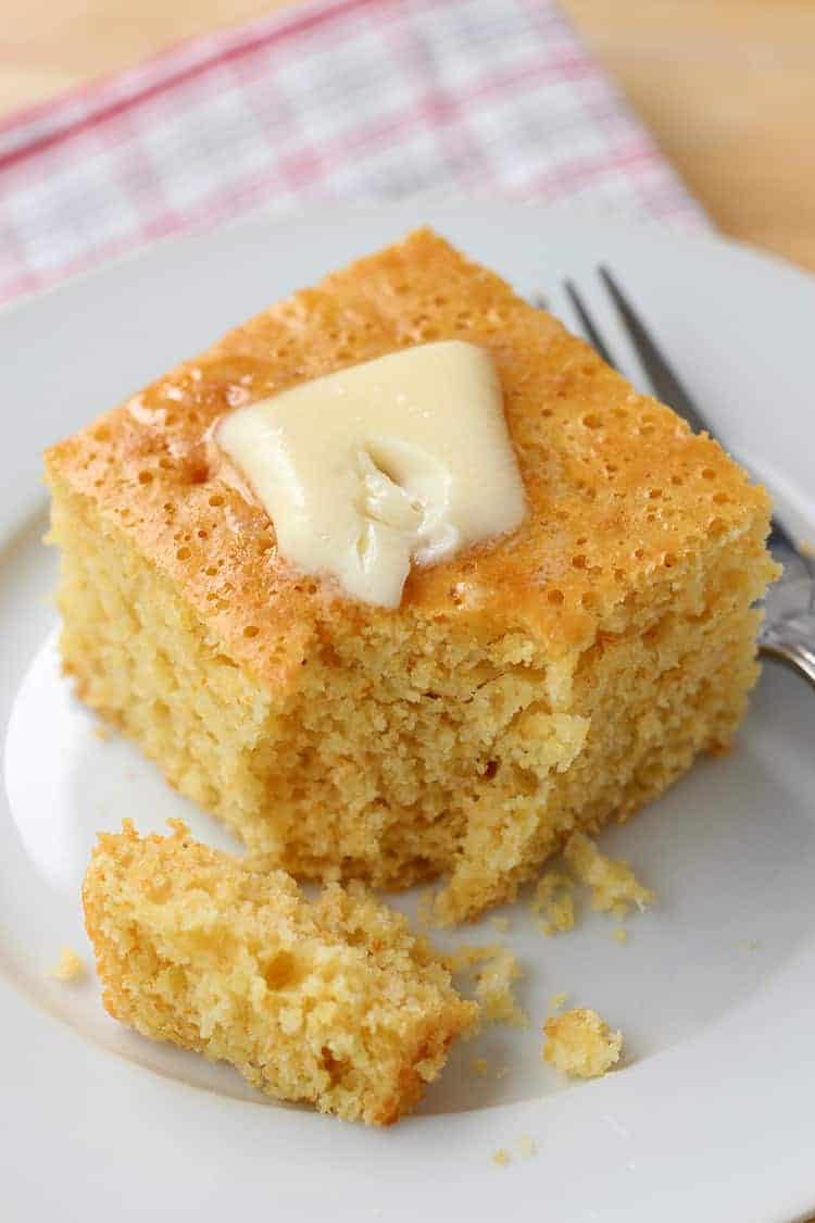 Close up of piece of cornbread with pat of butter melting on top.