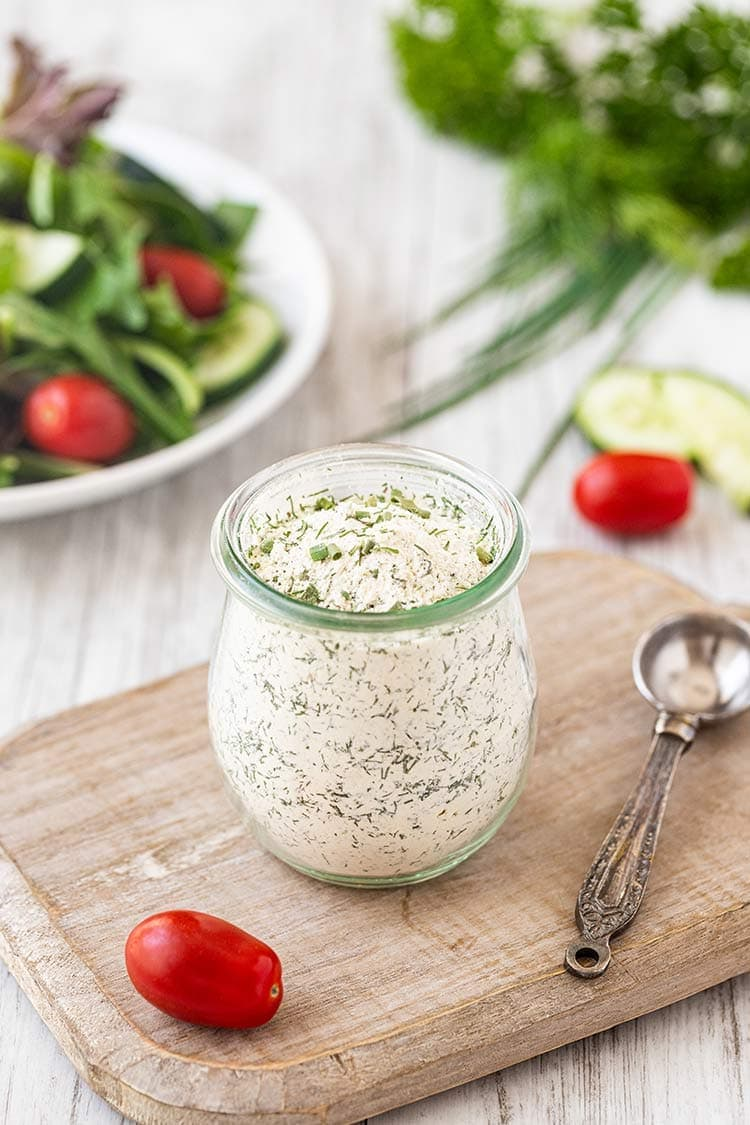 Homemade Ranch Dressing Mix in a small glass jar, sitting on top of a cutting board, with green salad and herbs in the background.