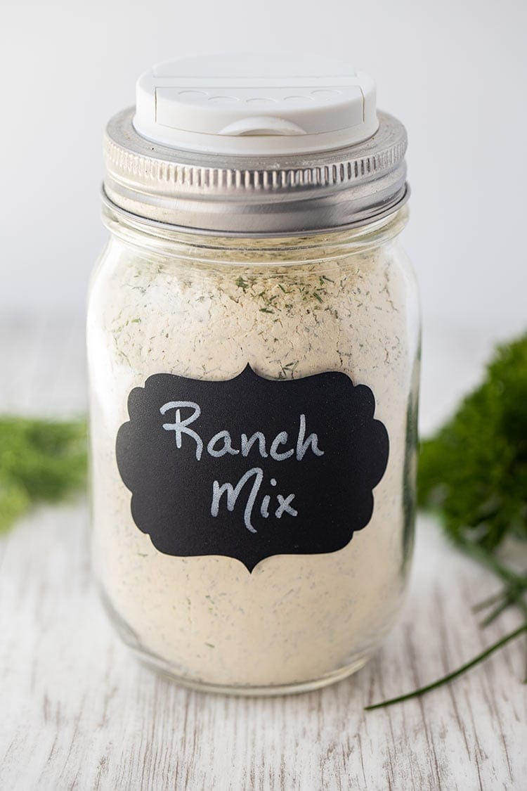 "Dry Ranch Seasoning Mix in a pint-size mason jar with a black chalkboard label on front that says ""Ranch Mix""."