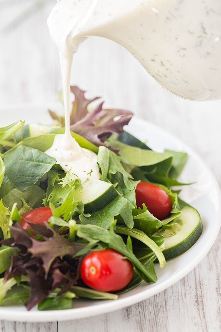 Picture of small glass pitcher of prepared ranch dressing being pour onto a basic green salad with tomatoes and cucumbers.