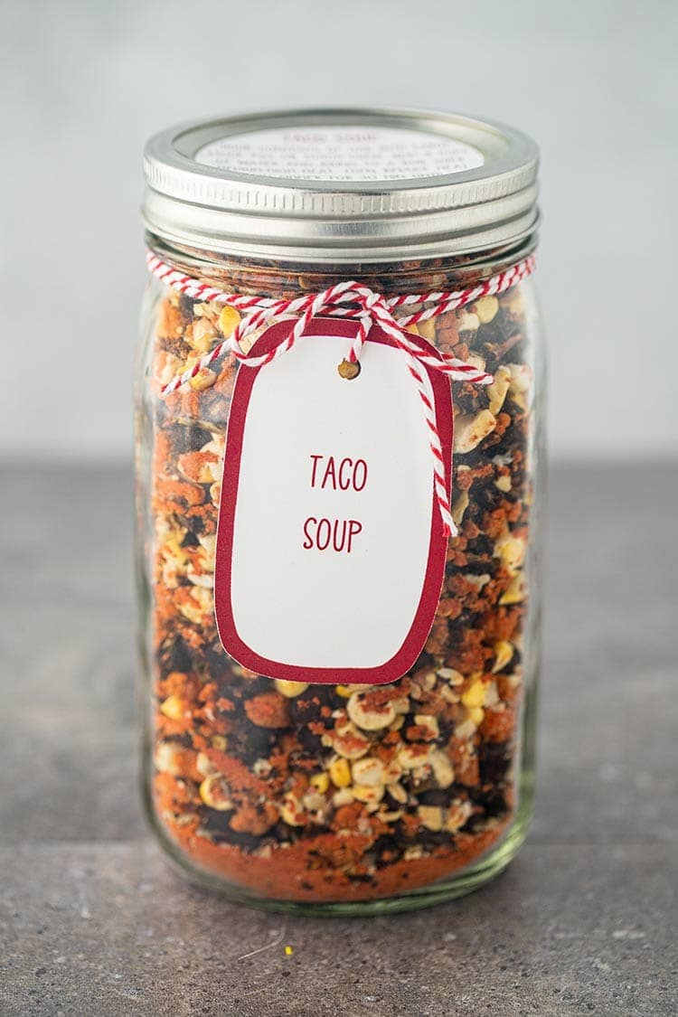 Picture of mason jar of dry ingredients for Taco Soup in a Jar with instruction label and gift tag
