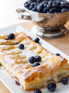 Make-Ahead Blueberry Cream Cheese Danish on a platter, with a collander of fresh blueberries in the background.