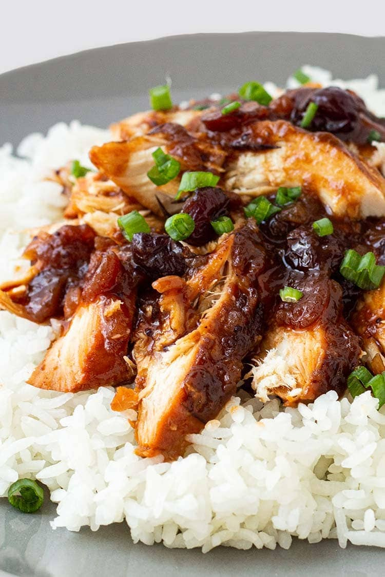 Closeup shot of cranberry catalina chicken on a bed of rice, on a gray plate.