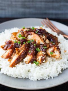 Cranberry Catalina Chicken on a bed of white rice on a gray plate, garnished with sliced green onions.