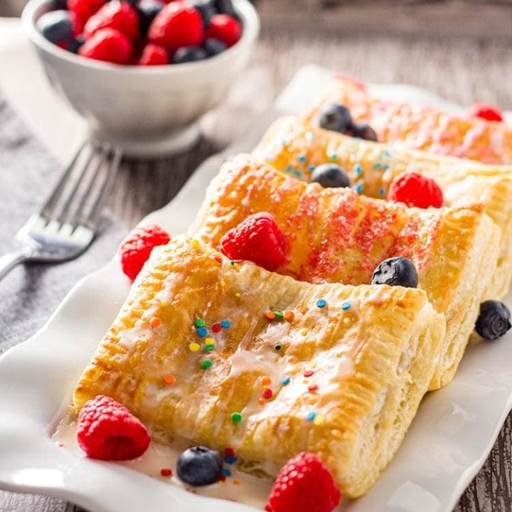 Easy Breakfast Pastries laid out on white rectangular plate on wooden tray with bowl of raspberries and blueberries in background.