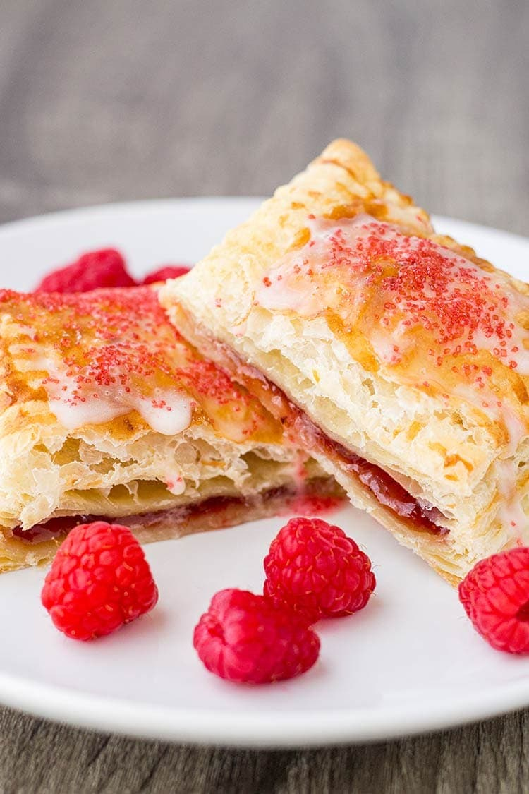 Raspberry breakfast pastry cut open on a plate, garnished with fresh raspberries.