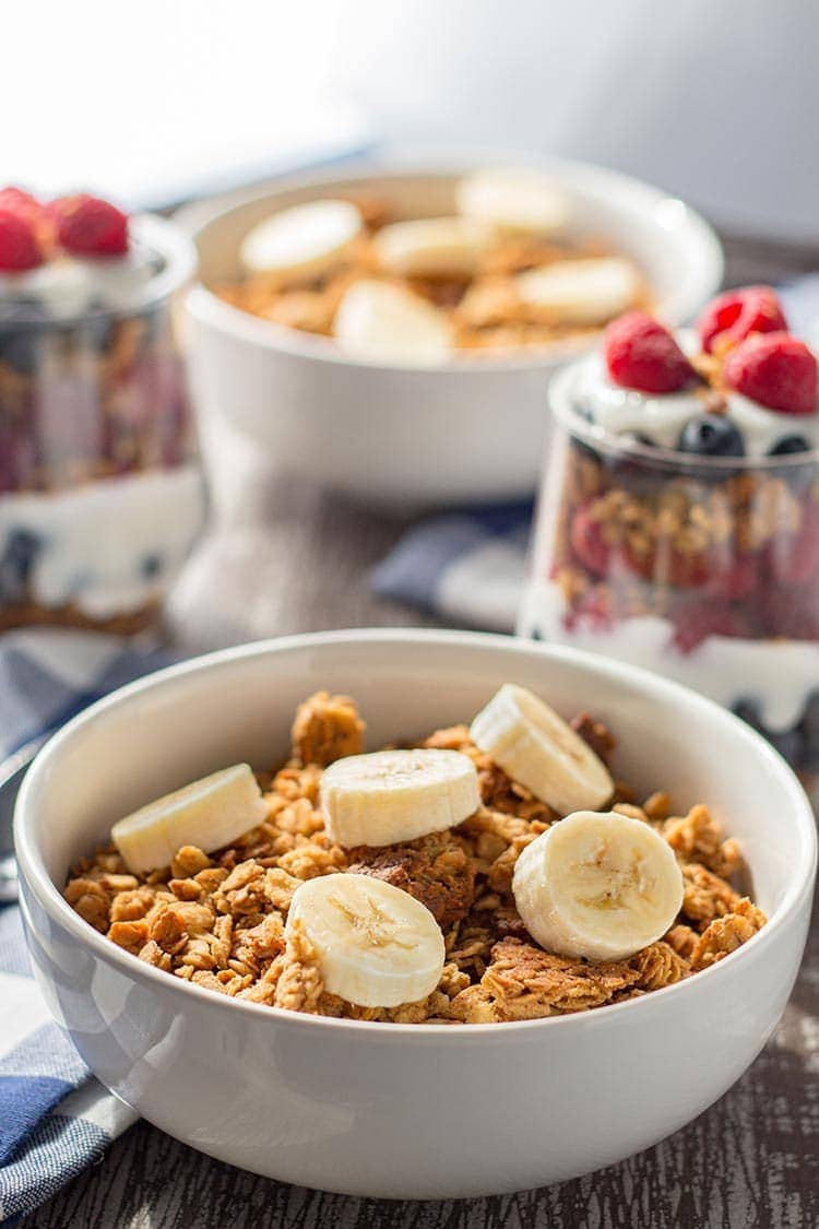 Bowls of Easy Peanut Butter Granola on table, topped with sliced bananas.