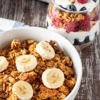 Bowl of Easy Peanut Butter Granola cereal topped with sliced bananas, with a fruit and yogurt granola parfait in the background.