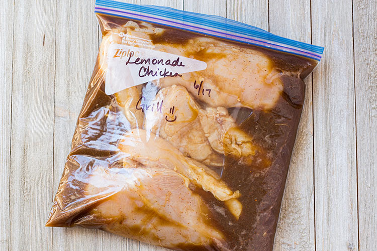 Grilled Lemonade Chicken Freezer Meal prepared in a ziptop freezer bag and laying on counter.