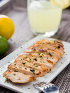 Grilled Lemonade Chicken sliced on a platter and garnished with lemon zest and parsley, with glass of lemonade in background.