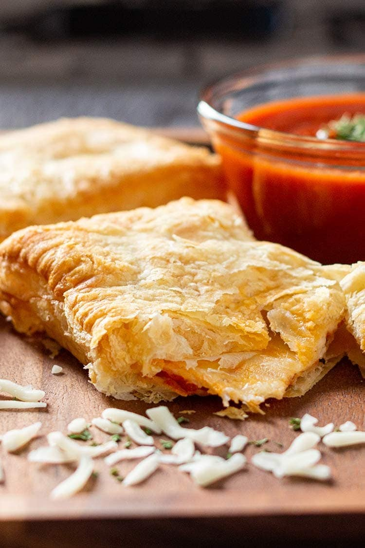 Closeup shot of Freezer-Friendly Homemade Pizza Pocket with melted cheese oozing out.