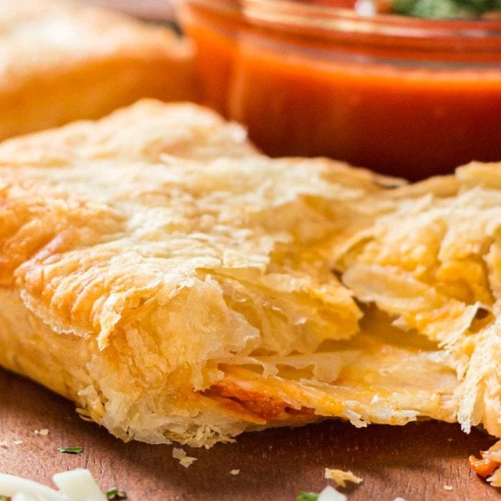 Puff pastry pizza pocket on tray with dipping sauce in background.