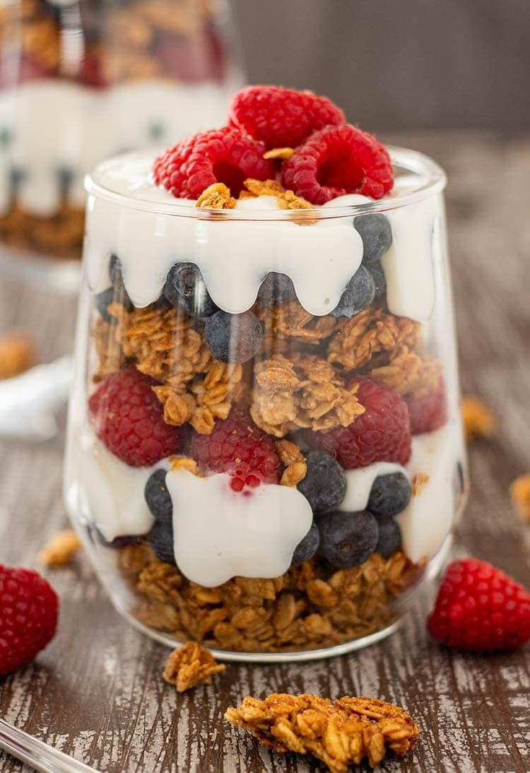Easy Granola Parfait in cup, layered with blueberries, raspberries and yogurt.