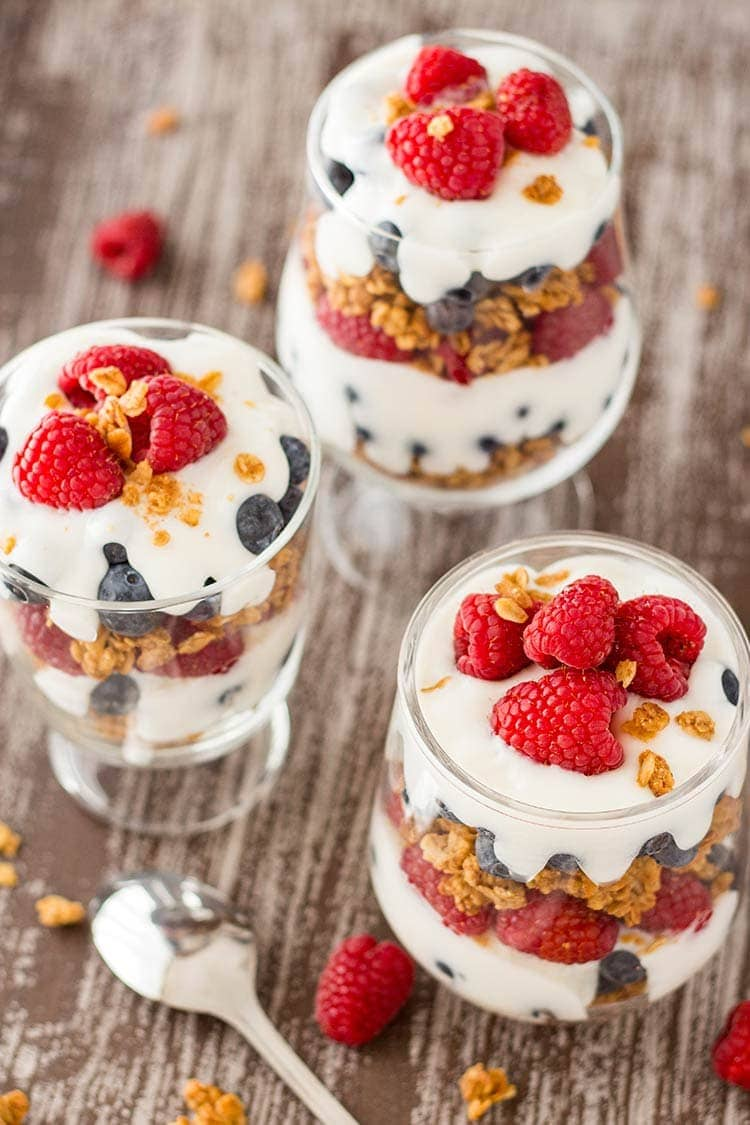 Trio of jars filled with Easy Granola Parfaits, made with granola, blueberries, raspberries and yogurt.