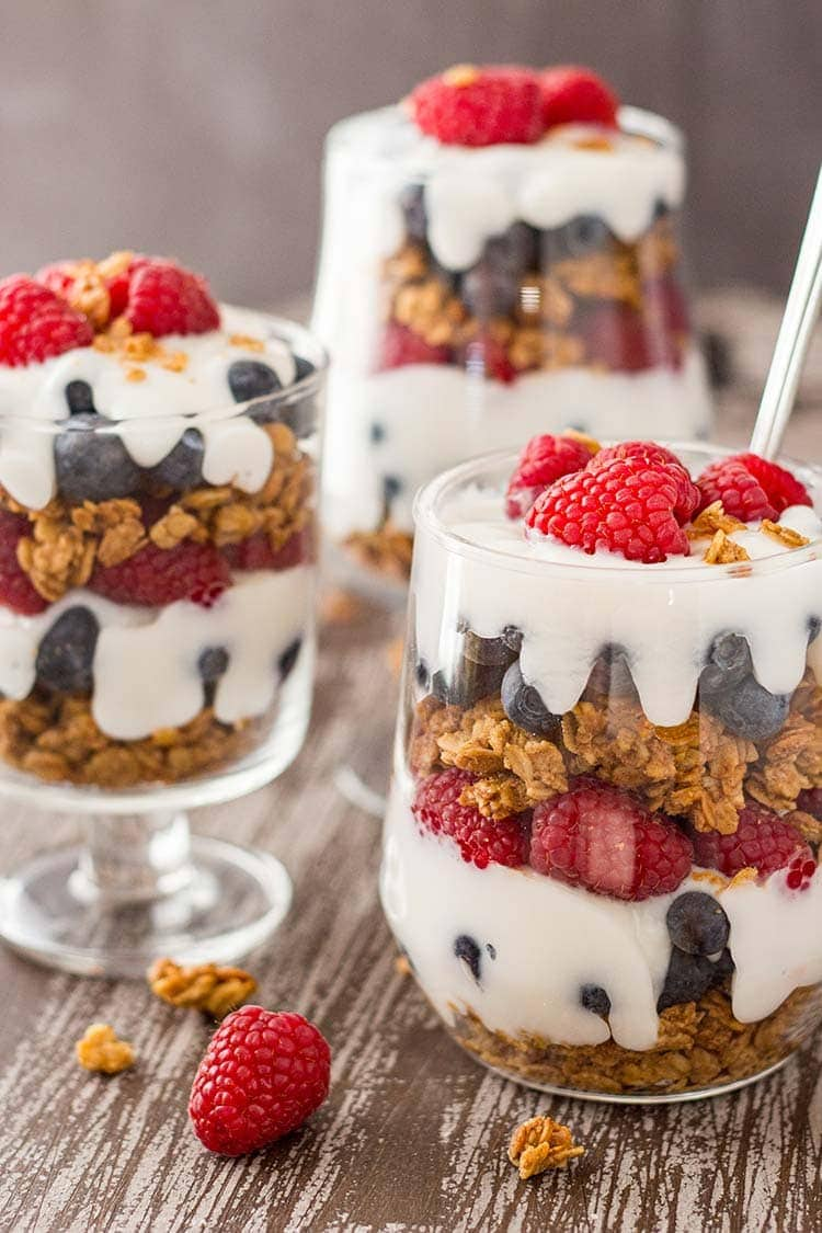 Three jars of Easy Granola Parfait garnished with raspberries, sitting on a tray.