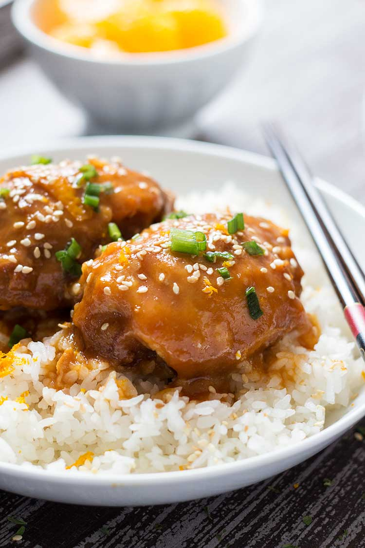 Sesame Orange Chicken thighs on a bed of rice, on plate with oranges in background.