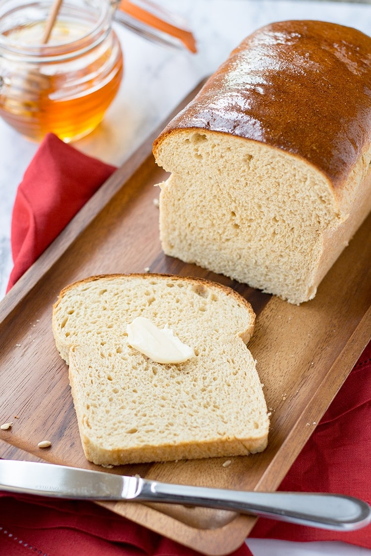Easy Homemade Honey Wheat Bread, sliced, on a cutting board, with a pat of butter on top.