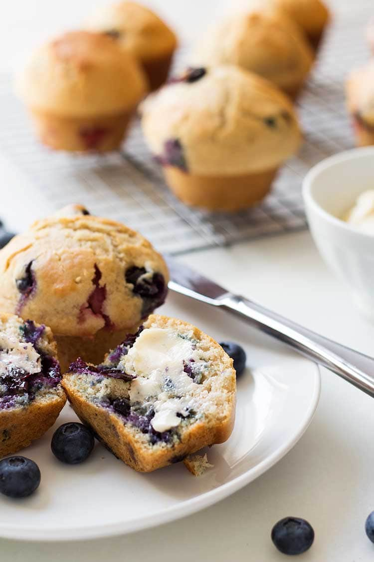 Blueberry muffins on a tray and plate, made from the Make-Ahead Muffin Mix recipe.