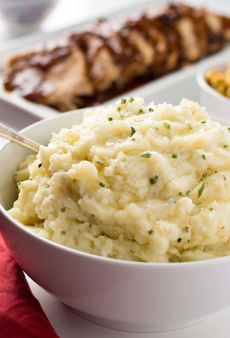 Garlic Herb Mashed Potatoes in a bowl on the table with dinner
