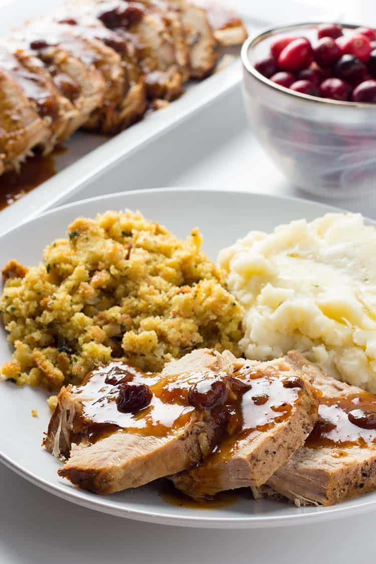 Spiced Cranberry Pork Roast dished up on a plate for a meal with mashed potatoes and stuffing
