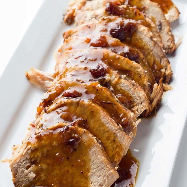 Spiced Cranberry Pork Roast sliced on a platter and covered with pan juice gravy