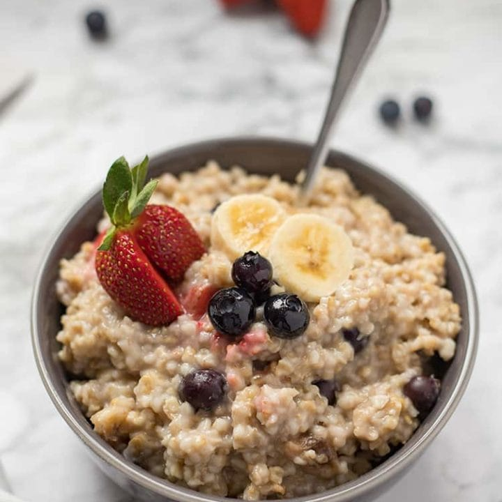 Bowl of steel cut oatmeal on marble background with cut fresh fruit