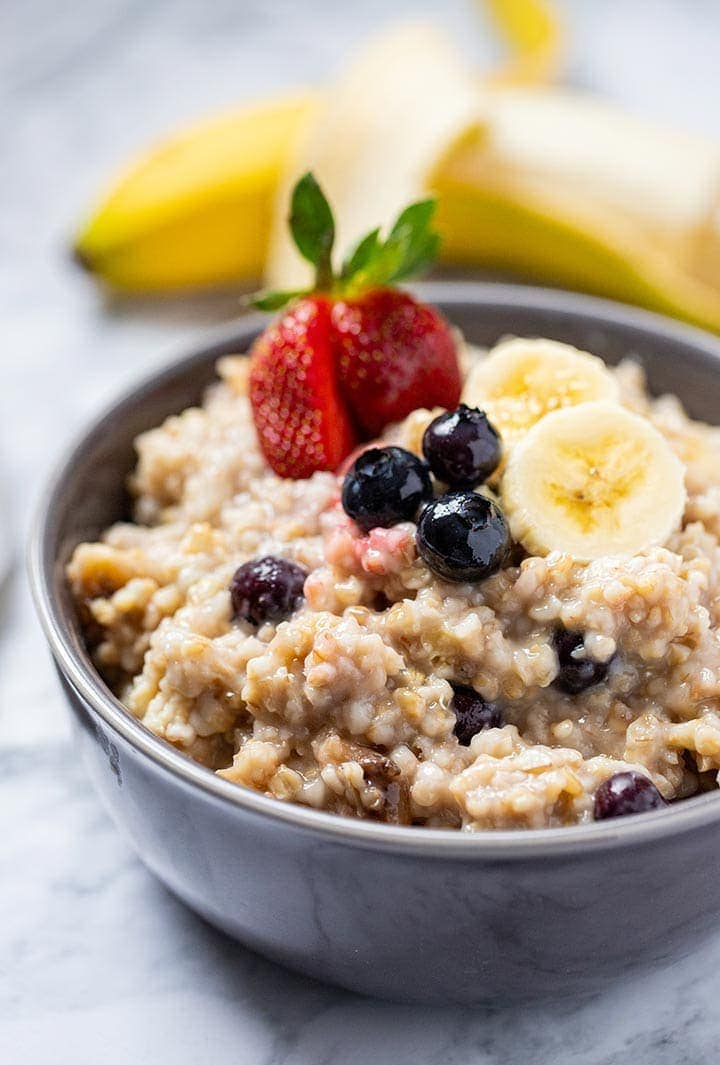 Instant Pot Easy Steel Cut Oats in a gray bowl, topped with fresh strawberries, blueberries and sliced banana.
