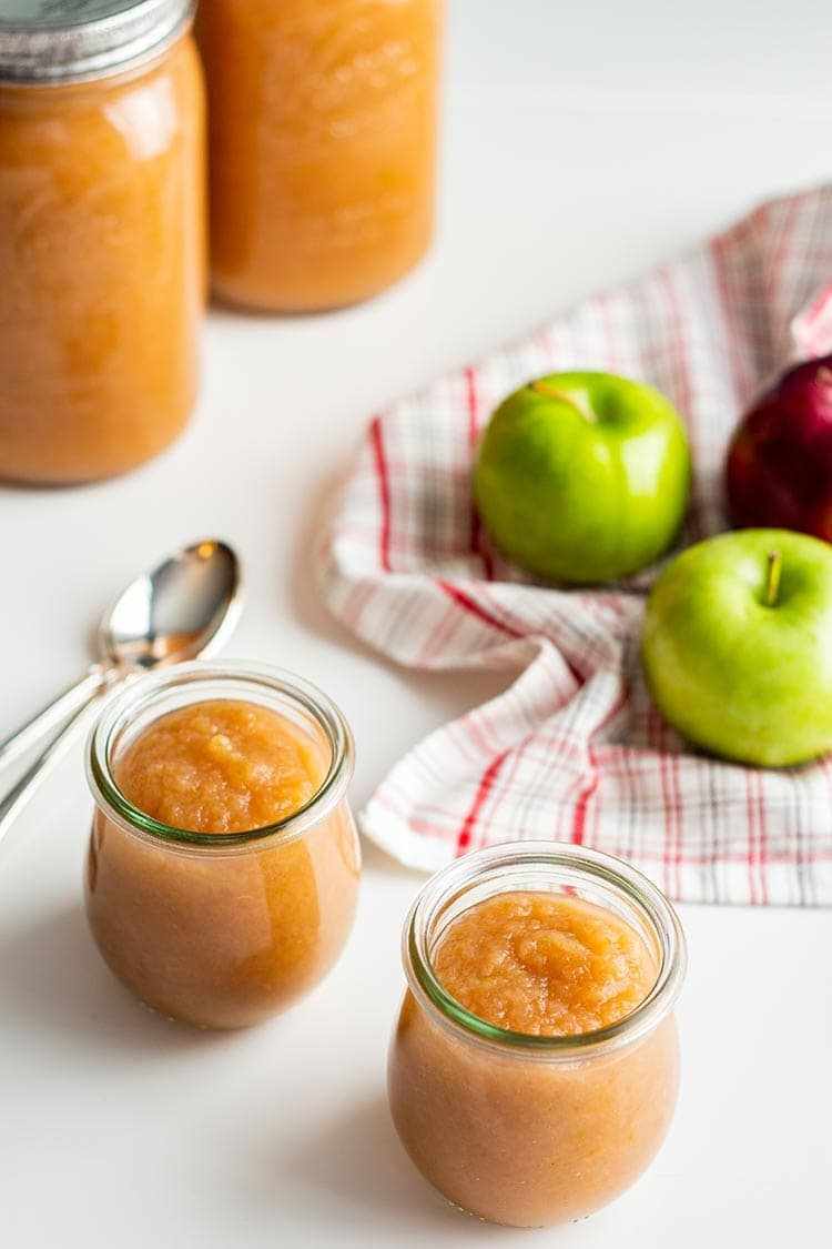 Jars of Instant Pot Apple Sauce on a white table with apples and towel in background.