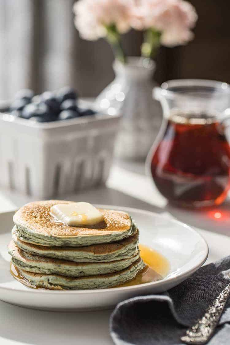 Leftover Oatmeal Blender Pancakes on table, with syrup and blueberries in background