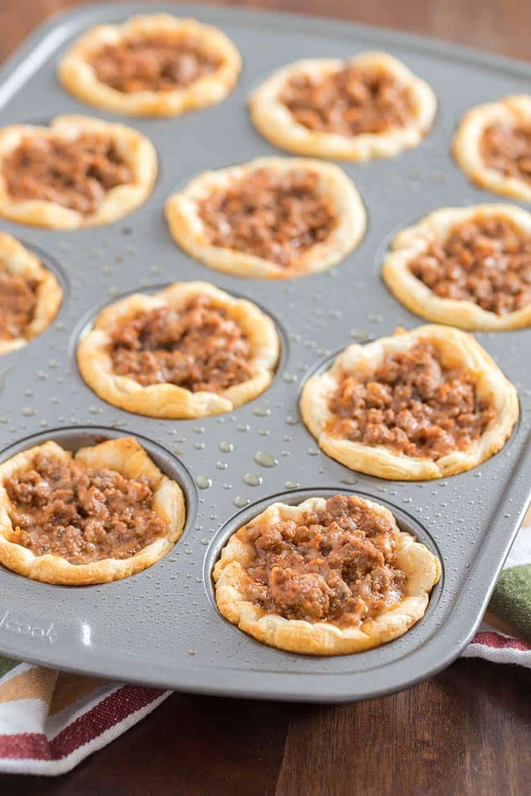 Savory Italian Biscuit Cups in muffin tin after baking but before final layer of cheese