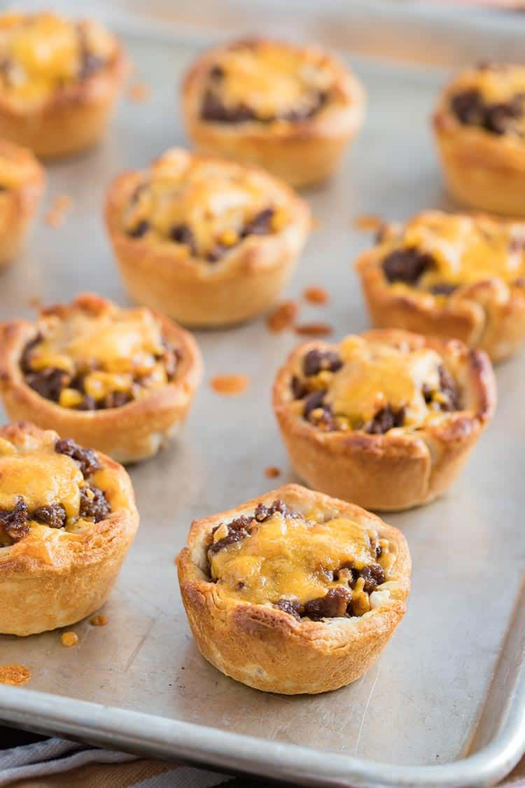 Beefy Barbecue Biscuit Cups baked on tray and topped with melted cheese ready to eat