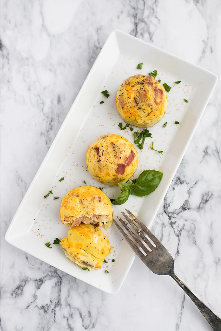 Overhead shot of Bacon Cheddar Egg Bites on rectangular white plate against marble background