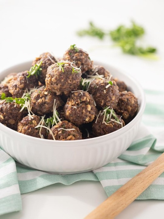 Easy Baked Freezer Meatballs piled in a white bowl and garnished with chopped parsley and Parmesan cheese.