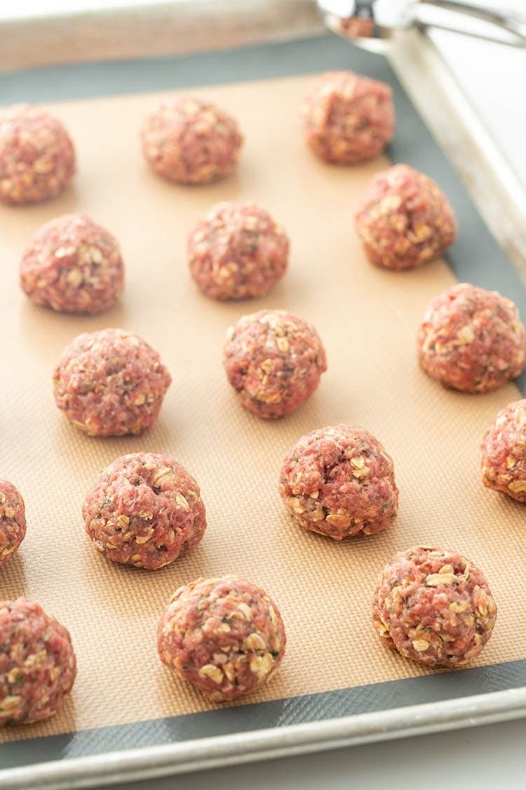 Easy Baked Freezer Meatballs portioned into balls on a baking tray and ready to be put in the oven.