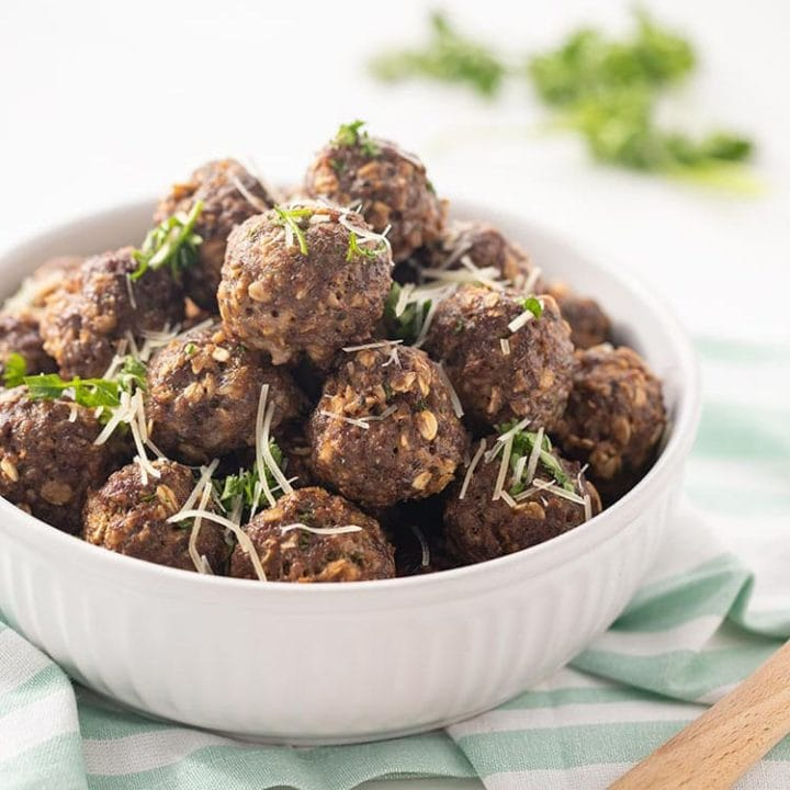 Easy Baked Freezer Meatballs piled in white bowl and garnished with parsley and Parmesan cheese.
