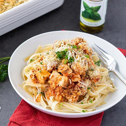 Easy Chicken Parmesan Bake served over linguine on white plate sitting atop a folded red fabric napkin