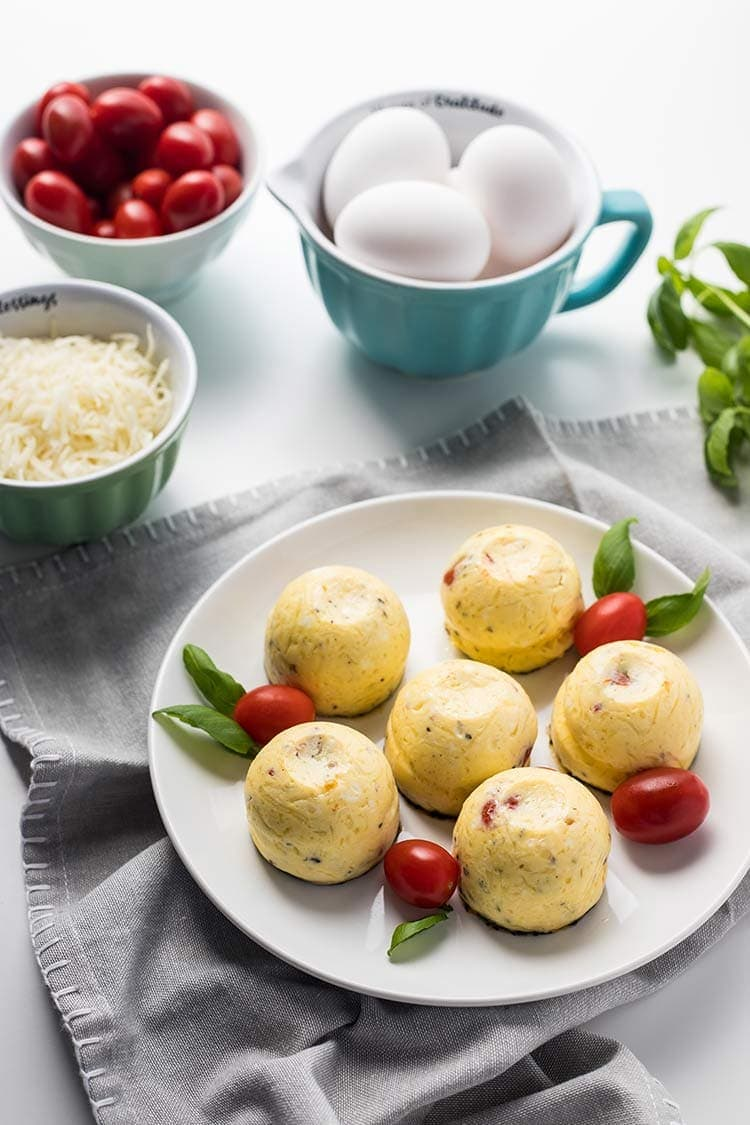 Instant Pot Caprese Egg Bites on plate next to bowls of eggs, tomatoes and shredded mozzarella cheese