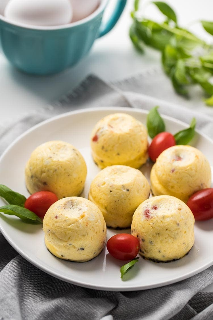 Instant Pot Caprese Egg Bites on a plate with fresh tomatoes and basil