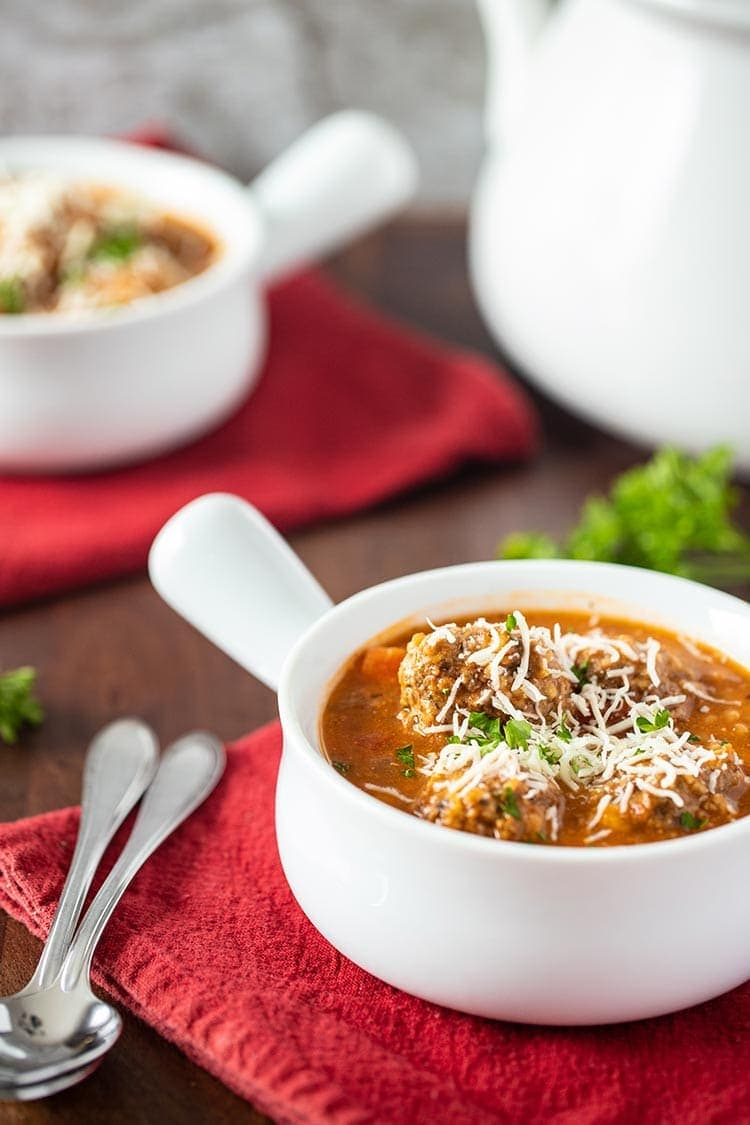 Instant Pot Hearty Meatball Soup in a white soup dish garnished with shredded cheese and fresh parsley in table setting