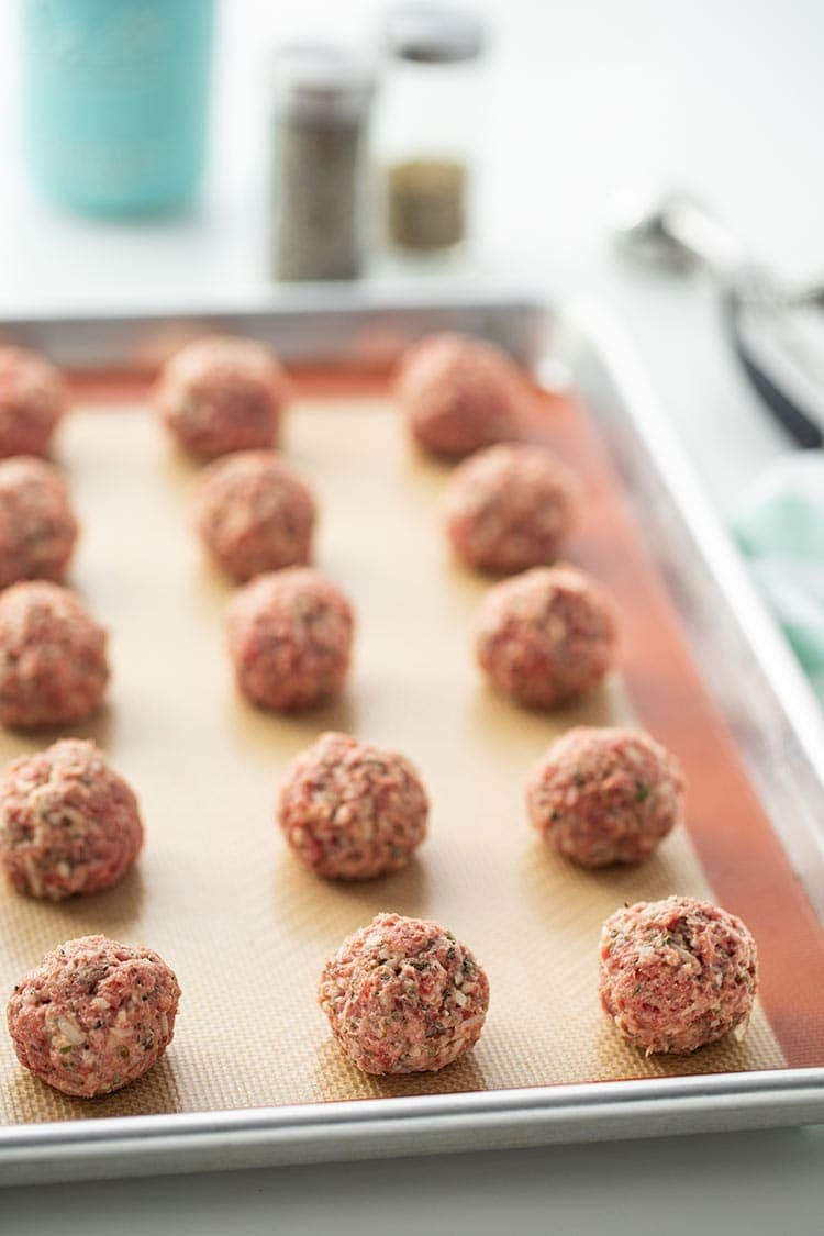 Easy Keto Meatballs portioned out on a baking sheet and ready to bake