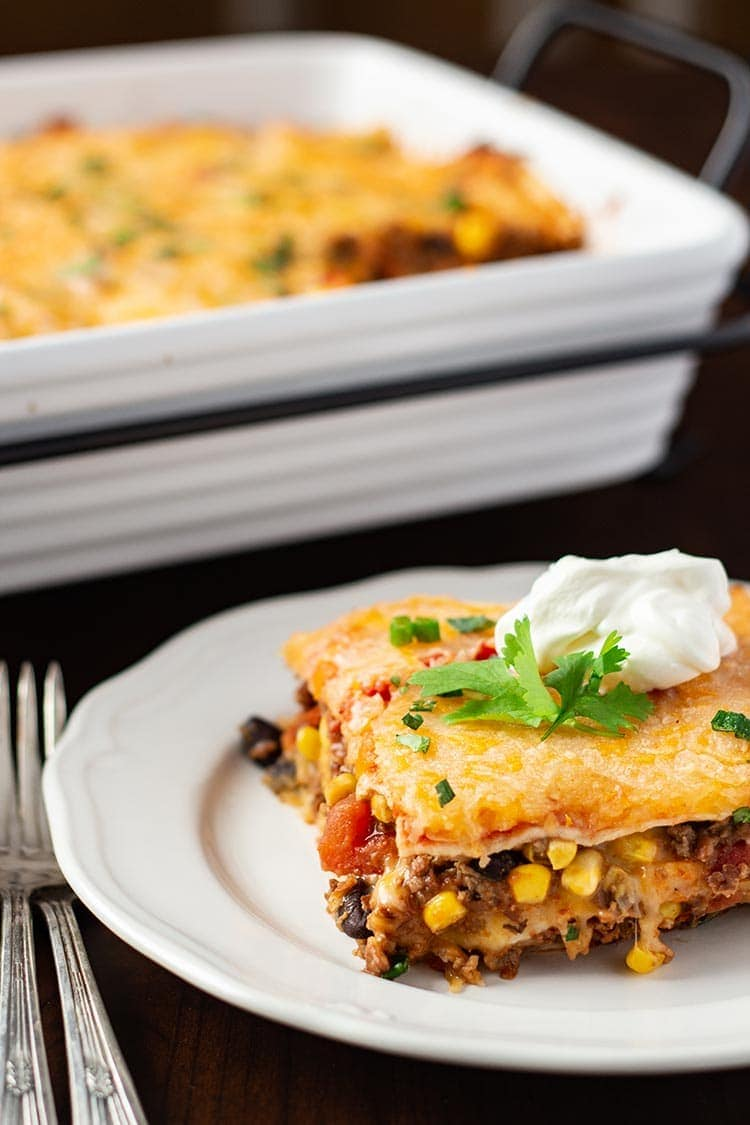 Make-Ahead Mexican Lasagna dished onto a white plate and garnished with sour cream and fresh cilantro