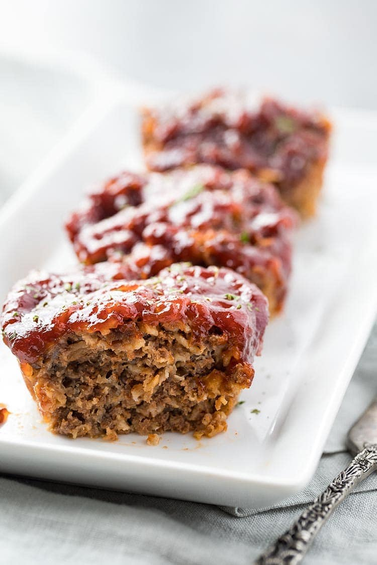 Mini Mozzarella Meatloaf Muffins lined up on a plate, with the first one cut in half to show the inside