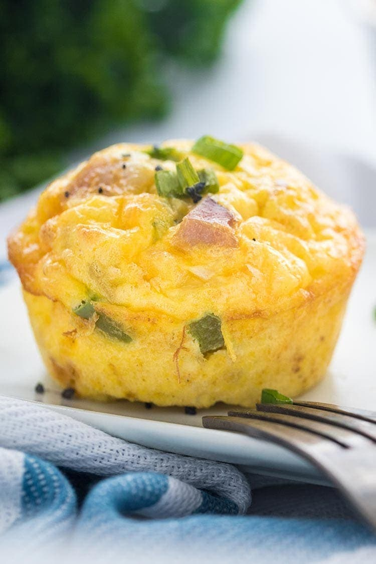 A Denver Omelet Egg Muffin on a white plate, garnished with sliced scallions and course sea salt.
