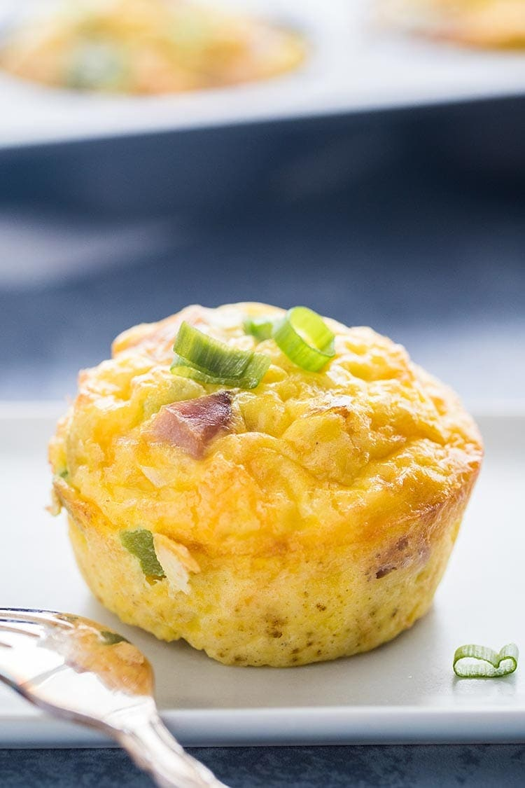 A single Denver Omelet Egg Muffin on a white plate on a blue background in front of a tray of egg muffins.
