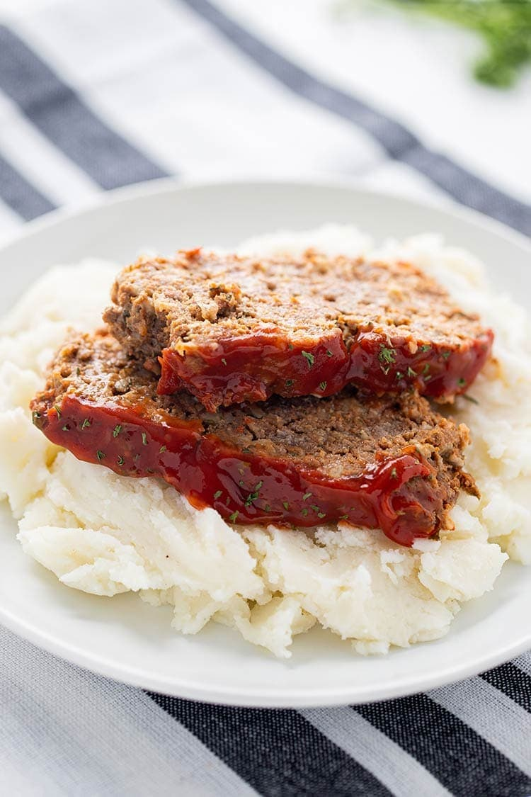 Two slices of Instant Pot Meatloaf on top of mashed potatoes and garnished with parsley.