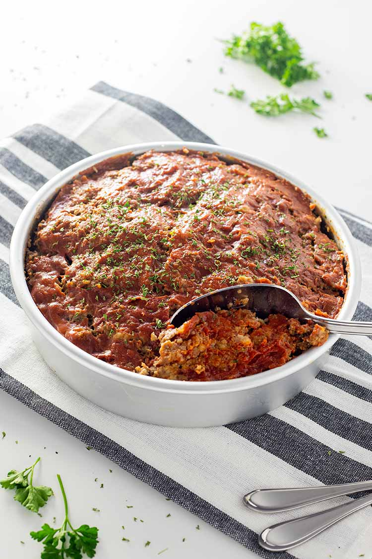 Gluten-free Instant Pot Meatloaf in a round cake pan with glaze and garnished with parsley.