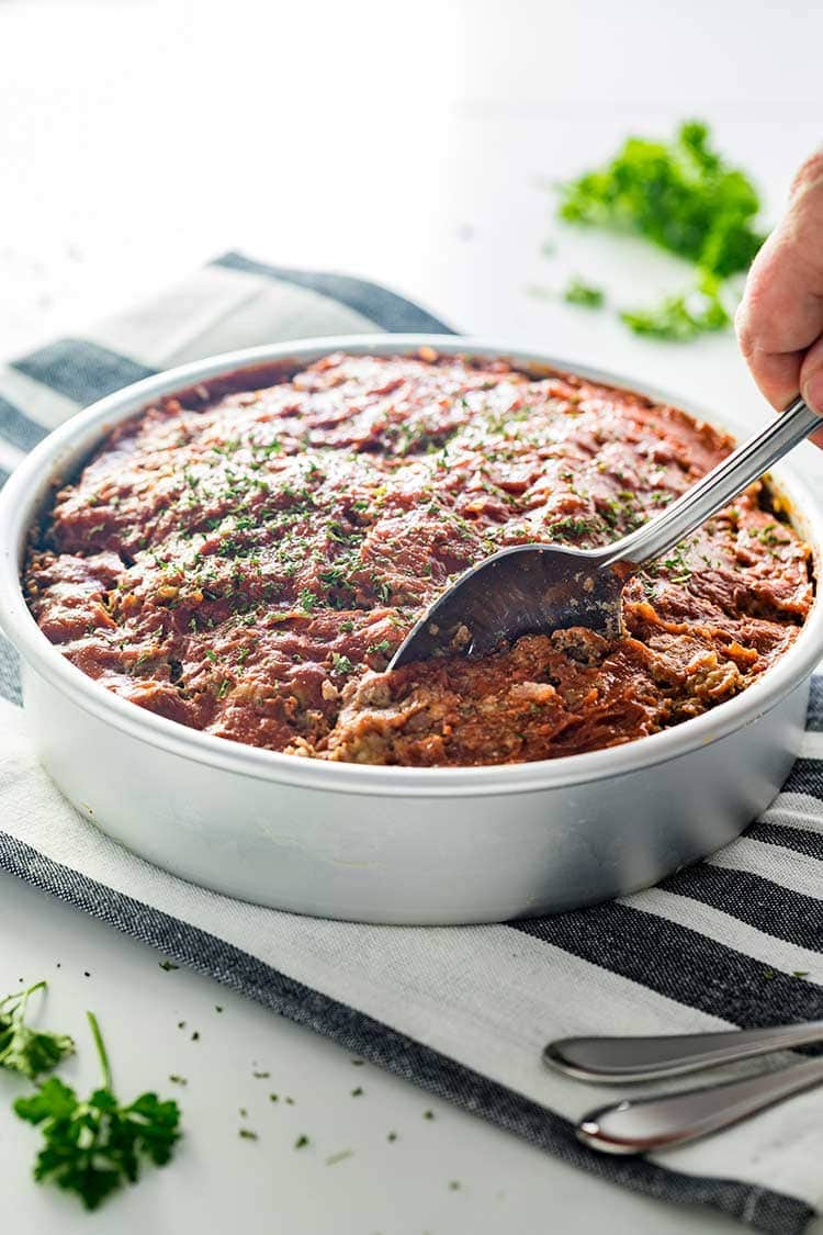 Instant Pot Meatloaf in a pan being dished up for dinner.