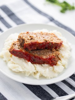 Two slices of Instant Pot Meatloaf set on top of a bed of mashed potatoes and garnished with chipped parsley.